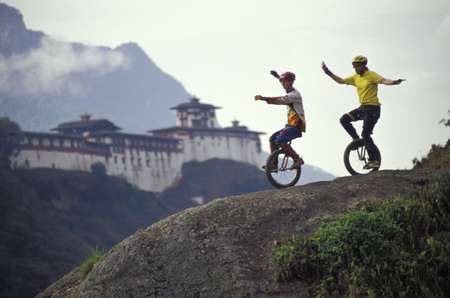 Unicyclists riding down hill photo