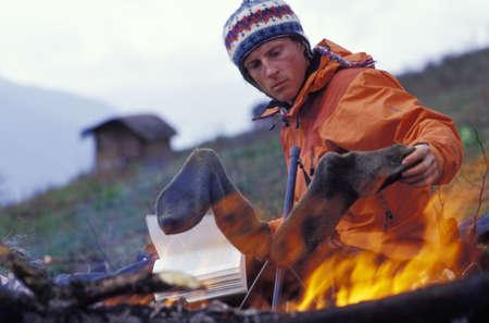 sean: Man drying socks by campfire Stock Photo