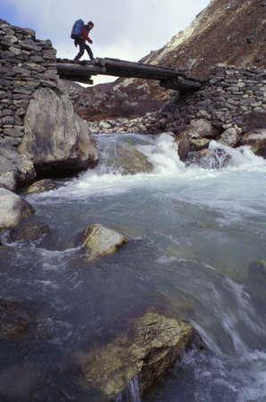 sherpa: Man crossing river on wooden bridge Stock Photo