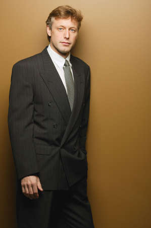 double breasted: Businessman leaning on wall