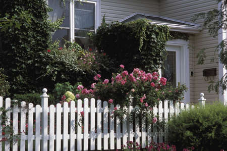 white picket fence: Flowers around house Stock Photo