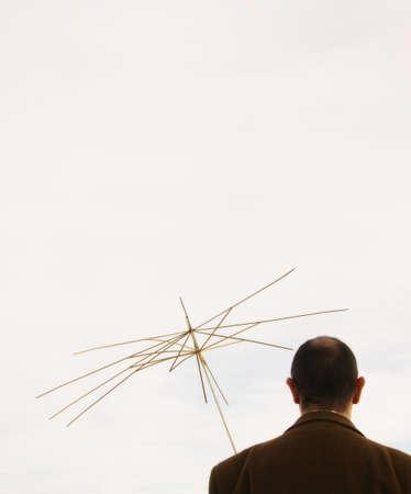 con man: Man holding useless umbrella Stock Photo