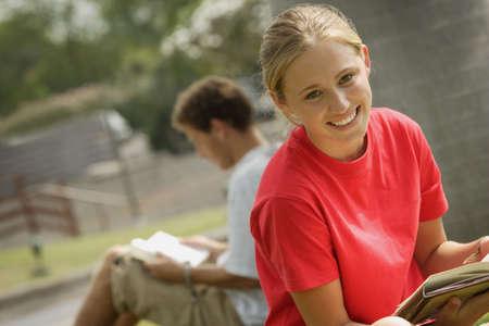 leer biblia: Estudiante sonriente lectura fuera Foto de archivo