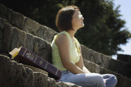 thinking woman: Bible in foreground with woman in background Stock Photo