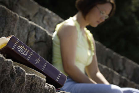 Bible in foreground with woman in background photo