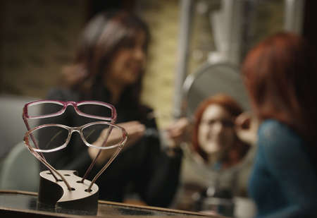 Glasses frames on display with woman trying on glasses with help in the background