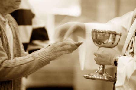 humility: Priest handing over communion wafer Editorial