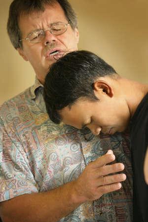 pastor: Man praying with teenager Stock Photo