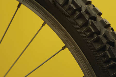 Part of a bicycle wheel against a yellow background photo