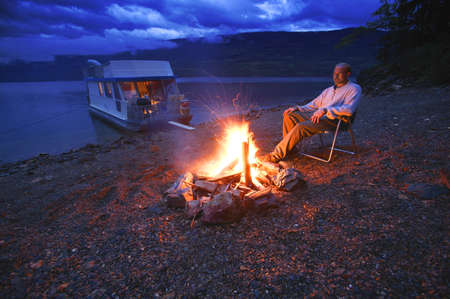 ponder: Man on shore relaxing at campfire
