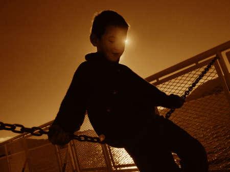 tanasiuk: Boy sitting on chain link