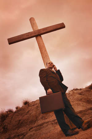 Businessman on phone leaning on a cross photo
