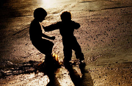 mischievous: Children pushing in puddle Stock Photo