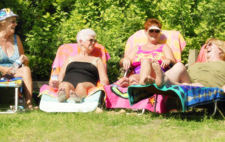 Group of four women sun tanning
