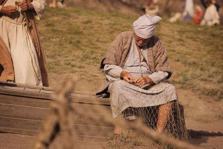 A fisherman mending his nets photo