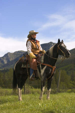 carson ganci: A woman on a horse against mountains Stock Photo