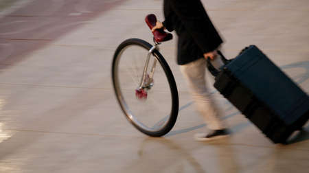 A person pushing a unicycle and pulling a suitcase