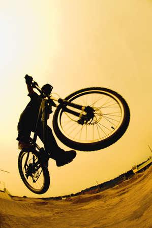 mountain bicycle: Silhouette di un ciclista contro un cielo giallo