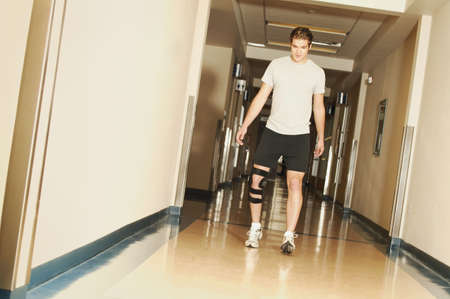 recovering: A young man walking with a knee brace in a hospital