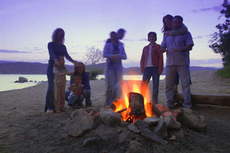 A group of friends and family around a bonfire on the beach