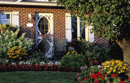 Front entrance of a home with flower gardens in the foreground