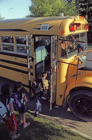 Kinderen voor het laden van een school bus Stockfoto