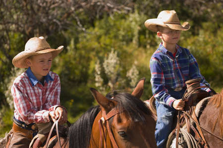 carson ganci: Two boys on horses Stock Photo