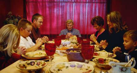 Familie bidden om Thanksgiving tafel  Stockfoto