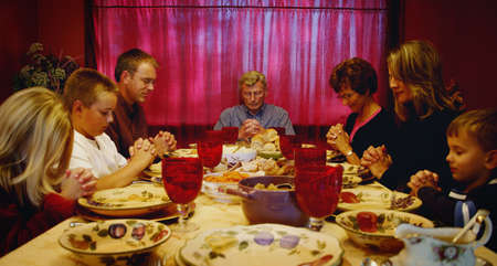 Family praying around Thanksgiving table photo