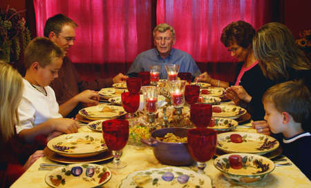 Family praying over Thanksgiving meal