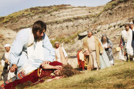 needy: Crowd watches as Jesus helps person lying on ground