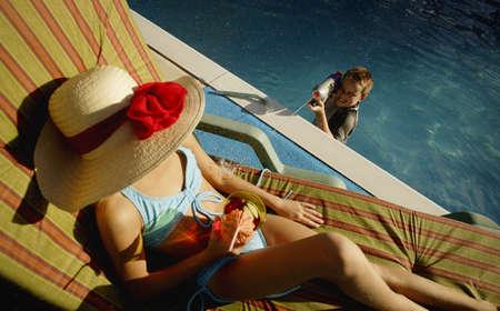 strip tease: Boy spraying woman sunbathing Stock Photo