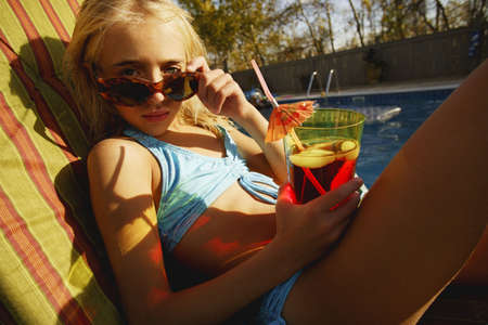 Child relaxes beside pool photo