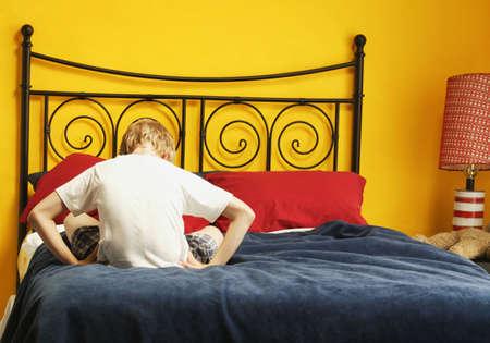 punishing: Child sulks on bed Stock Photo