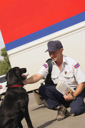 don hammond: Mail carrier pets dog Stock Photo