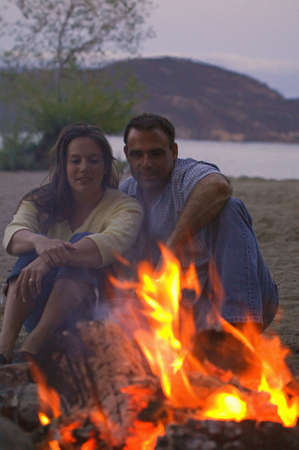 carson ganci: Couple sitting by fire Stock Photo