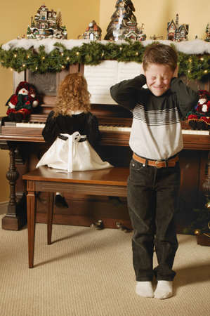 upright piano: Boy cringes at girls music