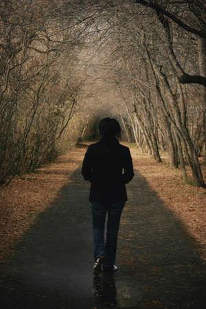 alone: Woman walks down a pathway