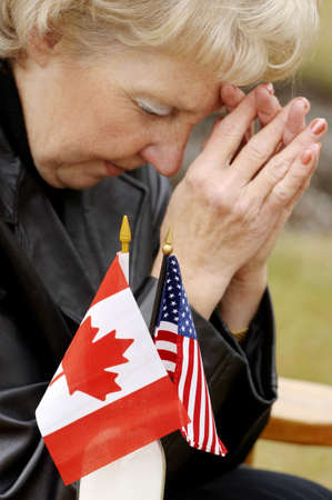 interceding: Woman praying over flags from different countries