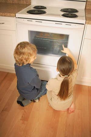 warkentin: Children watching the oven Stock Photo