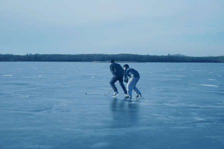 frozen lake: Playing hockey together Stock Photo