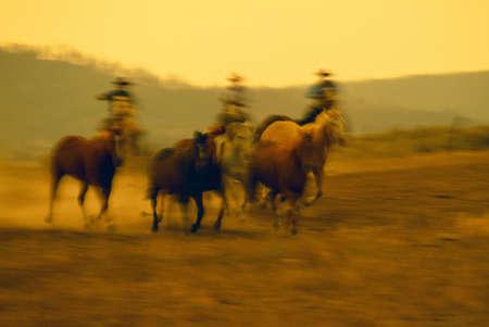 Cowboys on horseback herding running horses, Ponderosa Ranch, soft focus.