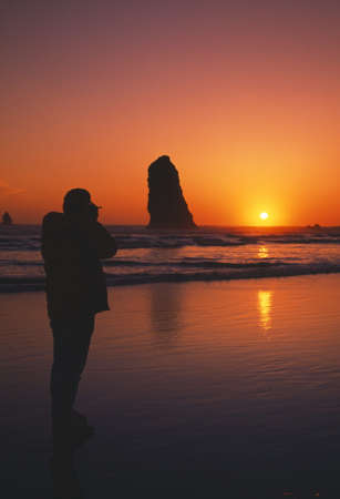 craig tuttle: Silhouette of person viewing sunset, rock formation, Cannon Beach. Stock Photo