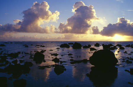 craig tuttle: Reflected sunset, clouds, and silhouetted rocks on beach, Rarotonga Island.