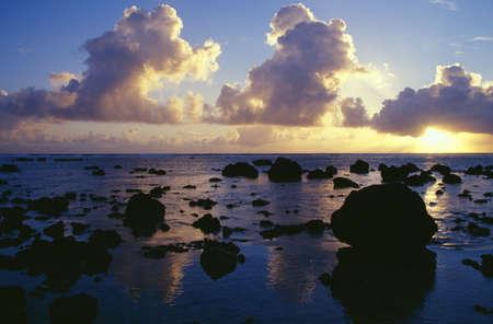 rarotonga: Tramonto riflesso, nuvole e Silhouette rocce sulla spiaggia, isola di Rarotonga.  Archivio Fotografico
