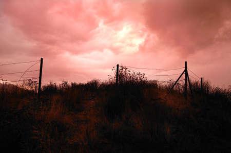 Dark sky over fenced in field Stock Photo - 5689293
