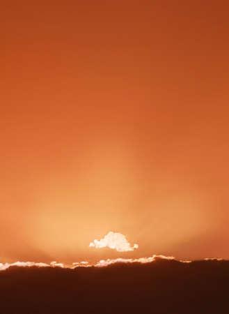 hues: Sun setting behind clouds