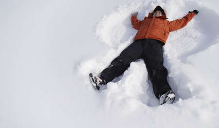 children at play: Boy making snow angel
