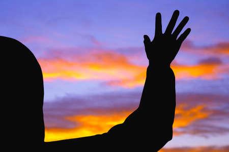 Silhouette of raised hand Stock Photo