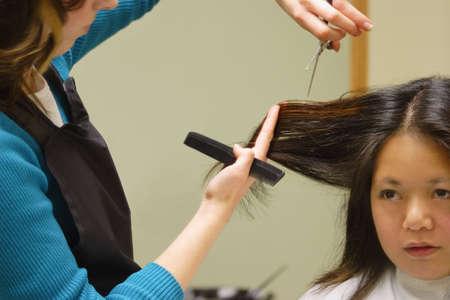 comb hair: Woman getting a haircut